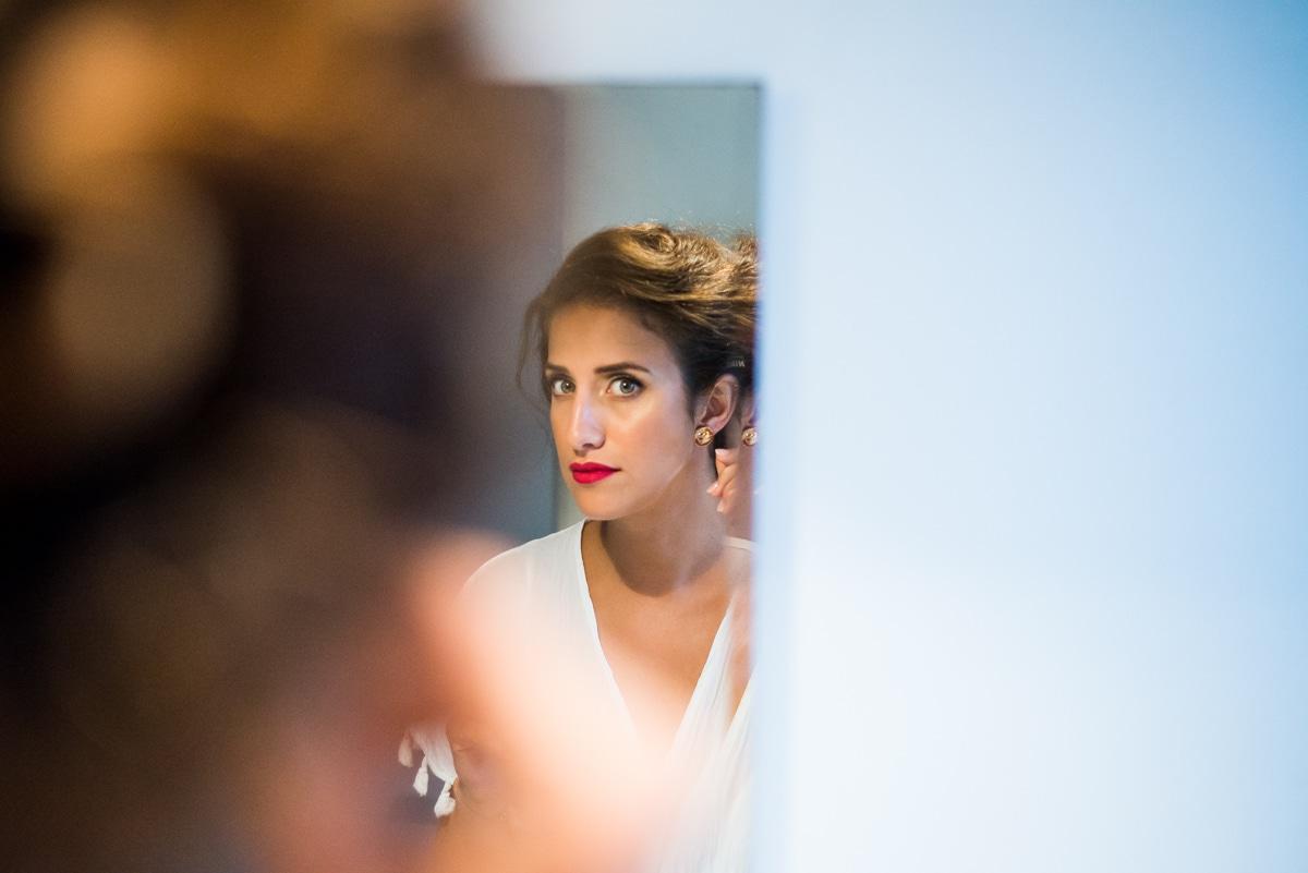 La mariée se prépare, elle porte un rouge à lèvre rouge mat très chic.