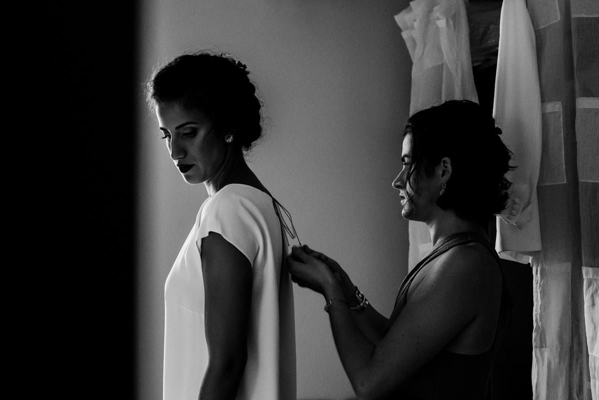 La témoin aide la mariée à fermer sa robe pour la cérémonie civile.