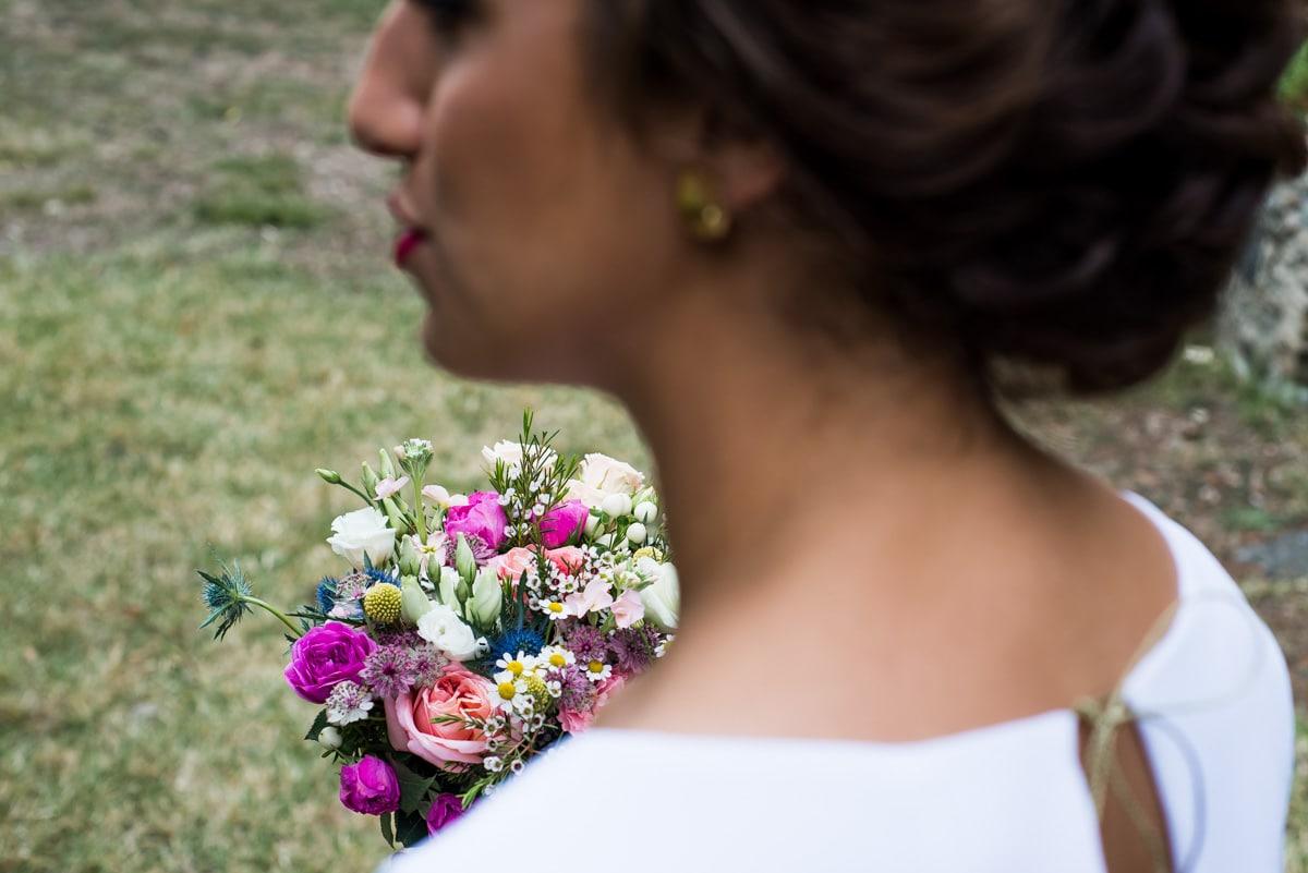 La mariée porte un bouquet de roses, de camomille et de chardon de Anouk Autier.