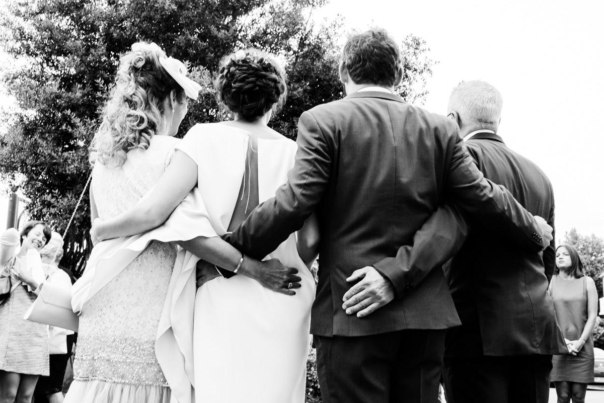 Les parents et les mariés se tiennent par la taille pour une photo de groupe devant la mairie de Pornic.