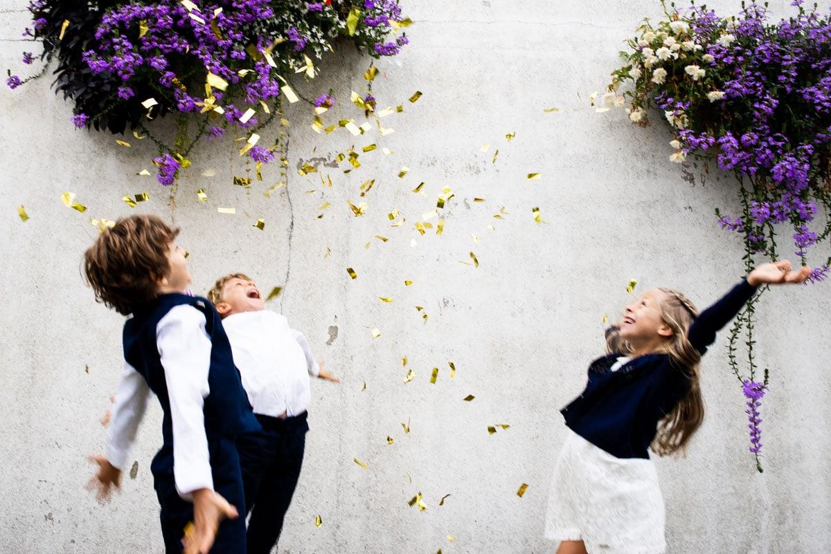 Les enfants d'honneurs jettent des confettis dorés en l'air