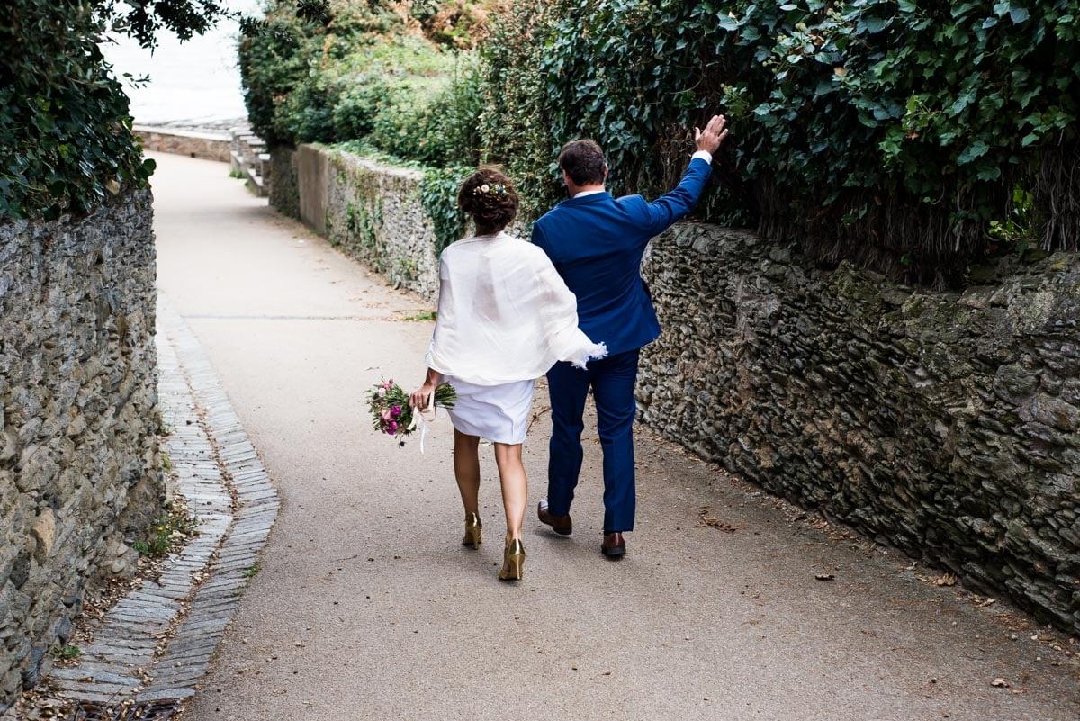 Les mariés marchent dans une ruelle de Sainte Marie sur mer.