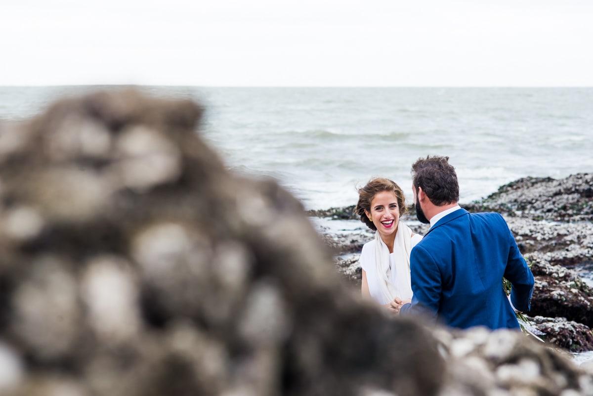 Les mariés s'amusent lors de la séance de photos de couple sur la plage de Pornic.
