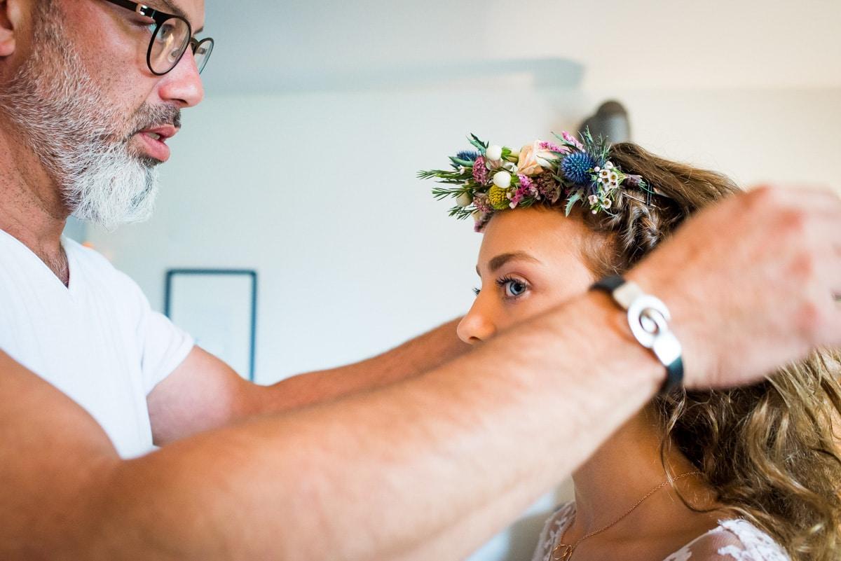 Le coiffeur accroche une couronne de fleurs dans les cheveux de la demoiselle d'honneur.