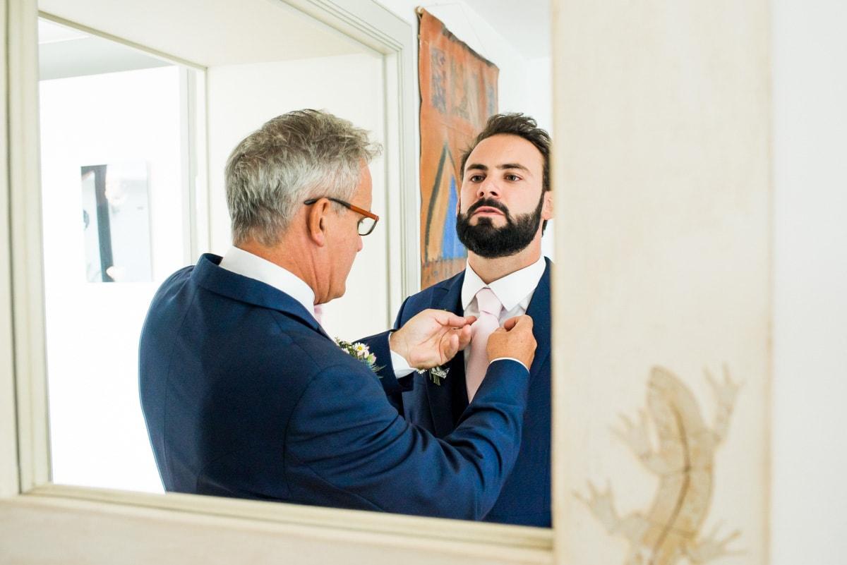 Le père du marié ajuste le noeud de cravate de son fils.