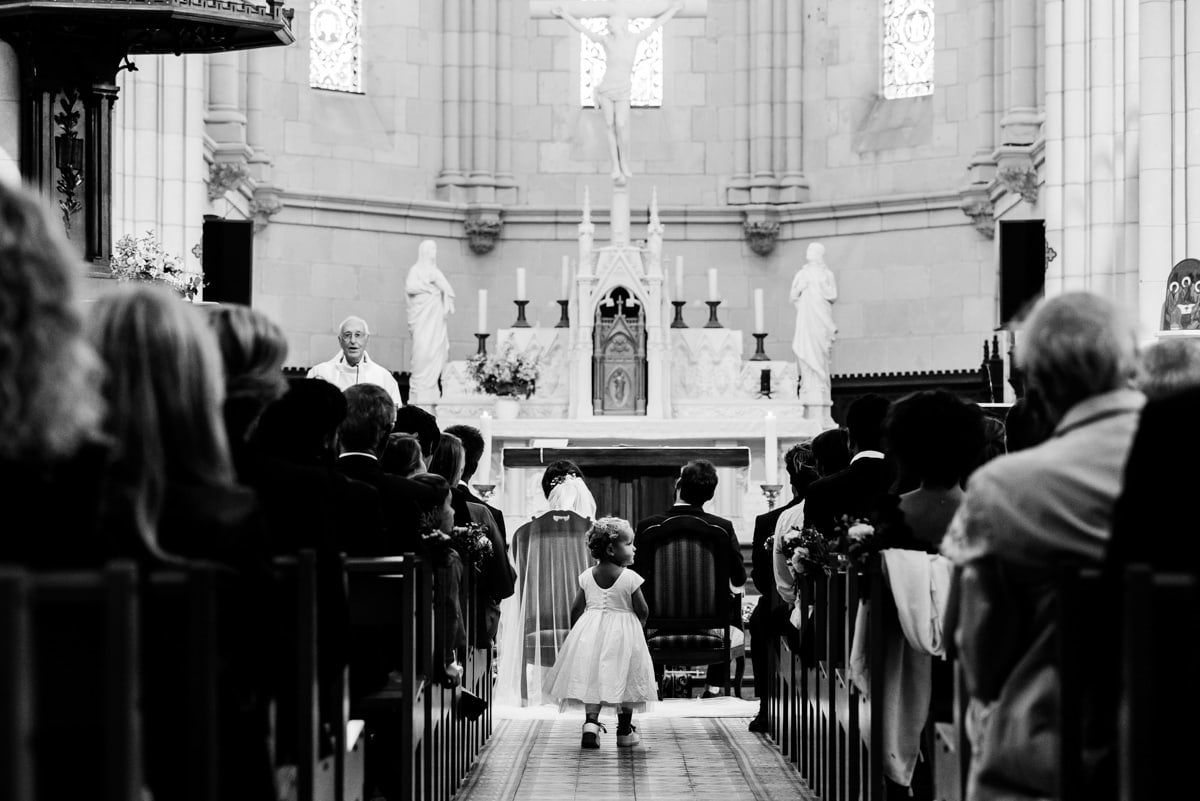 une petite fille se promène dans la travée de l'Eglise pendant le mariage chic en Loire Atlantique.