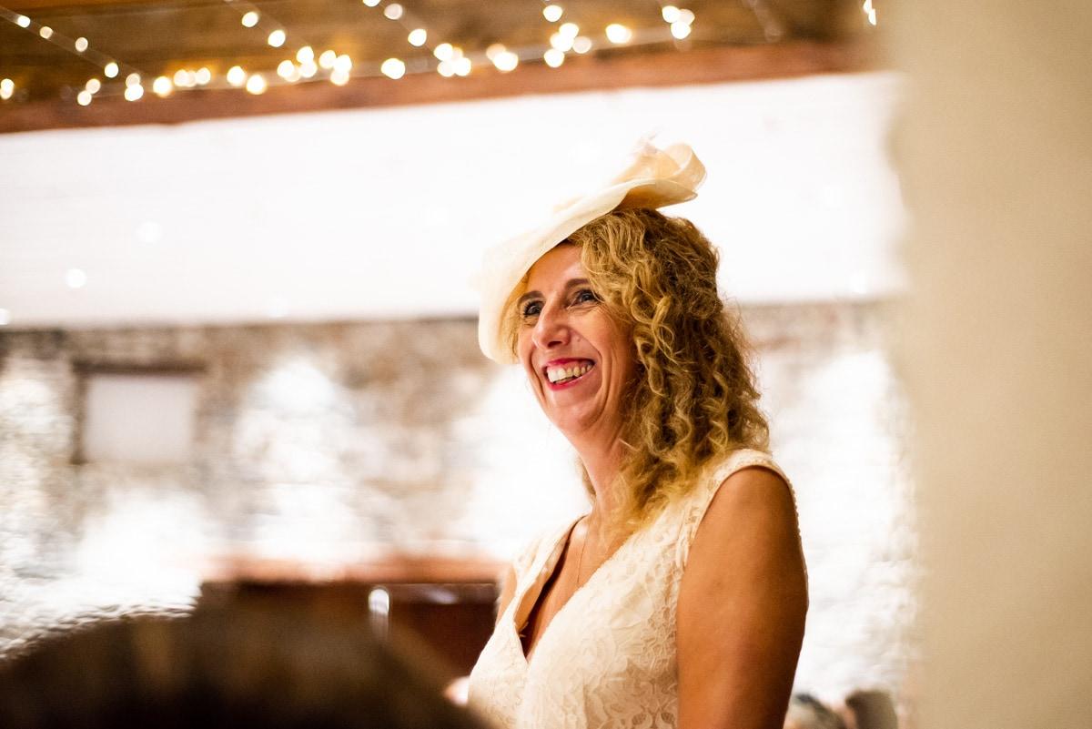 La mère de la mariée écoute un discours et sourit.