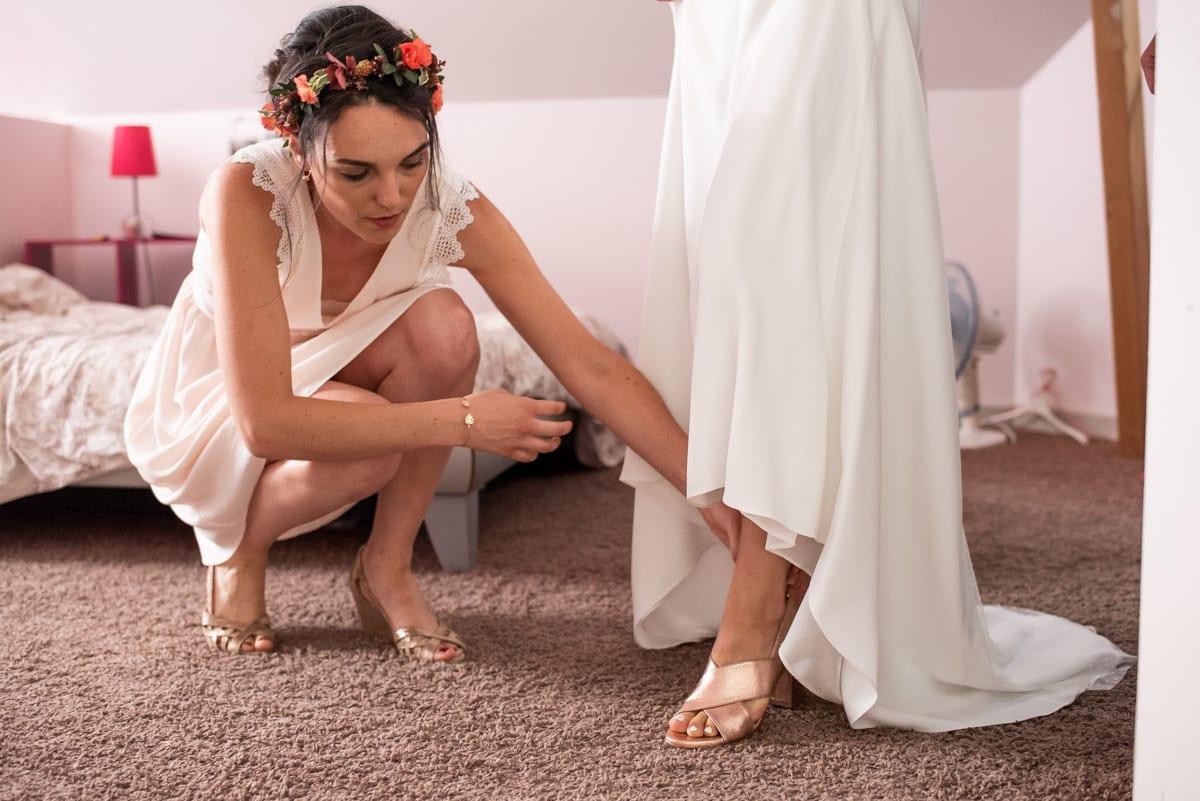La mariée glisse ses escarpins de mariage cuivré avec sa témoin à Rochefort sur Loire.
