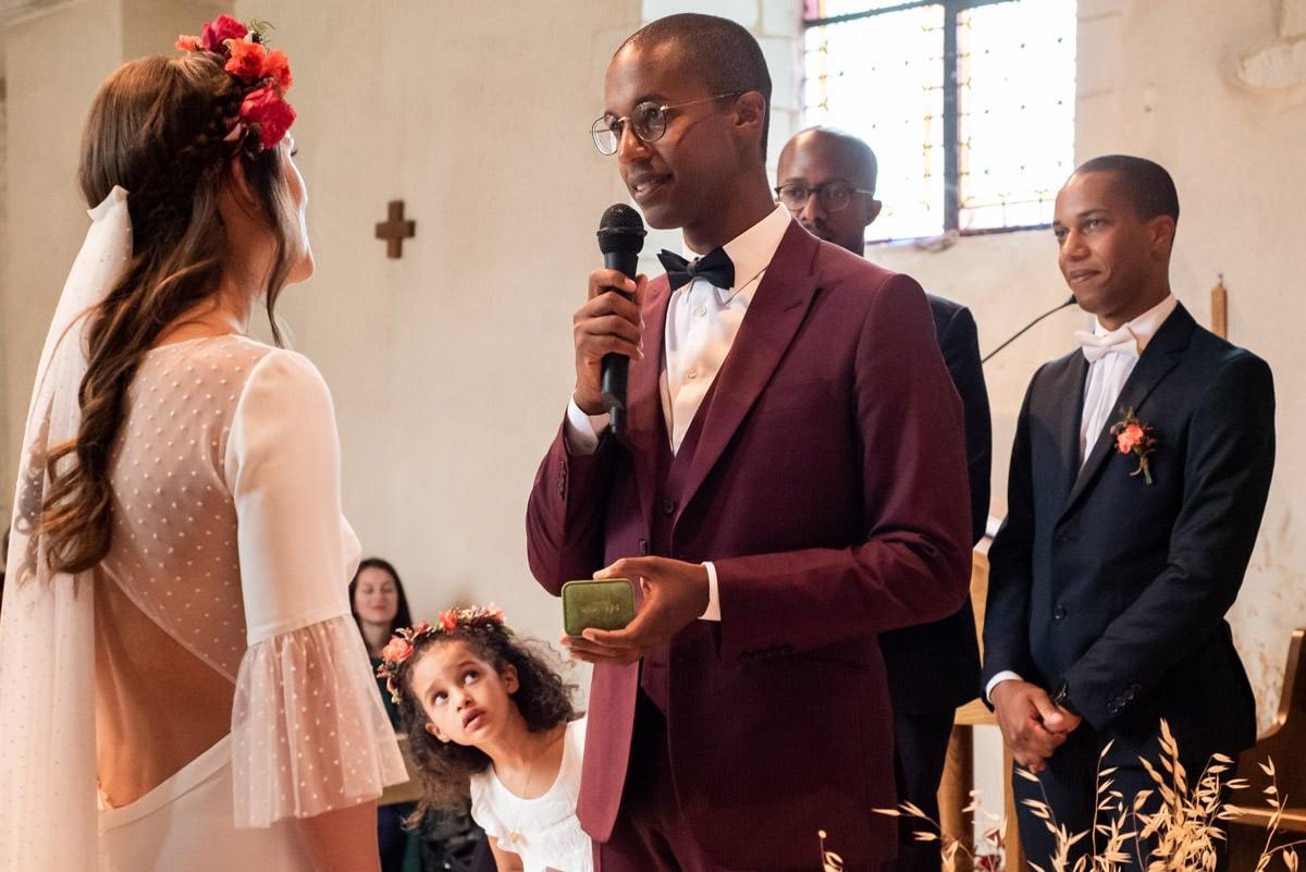 Echange des alliances entre les mariés à l'Eglise de Beaucouzé, une petite fille indiscrète se glisse entre eux.
