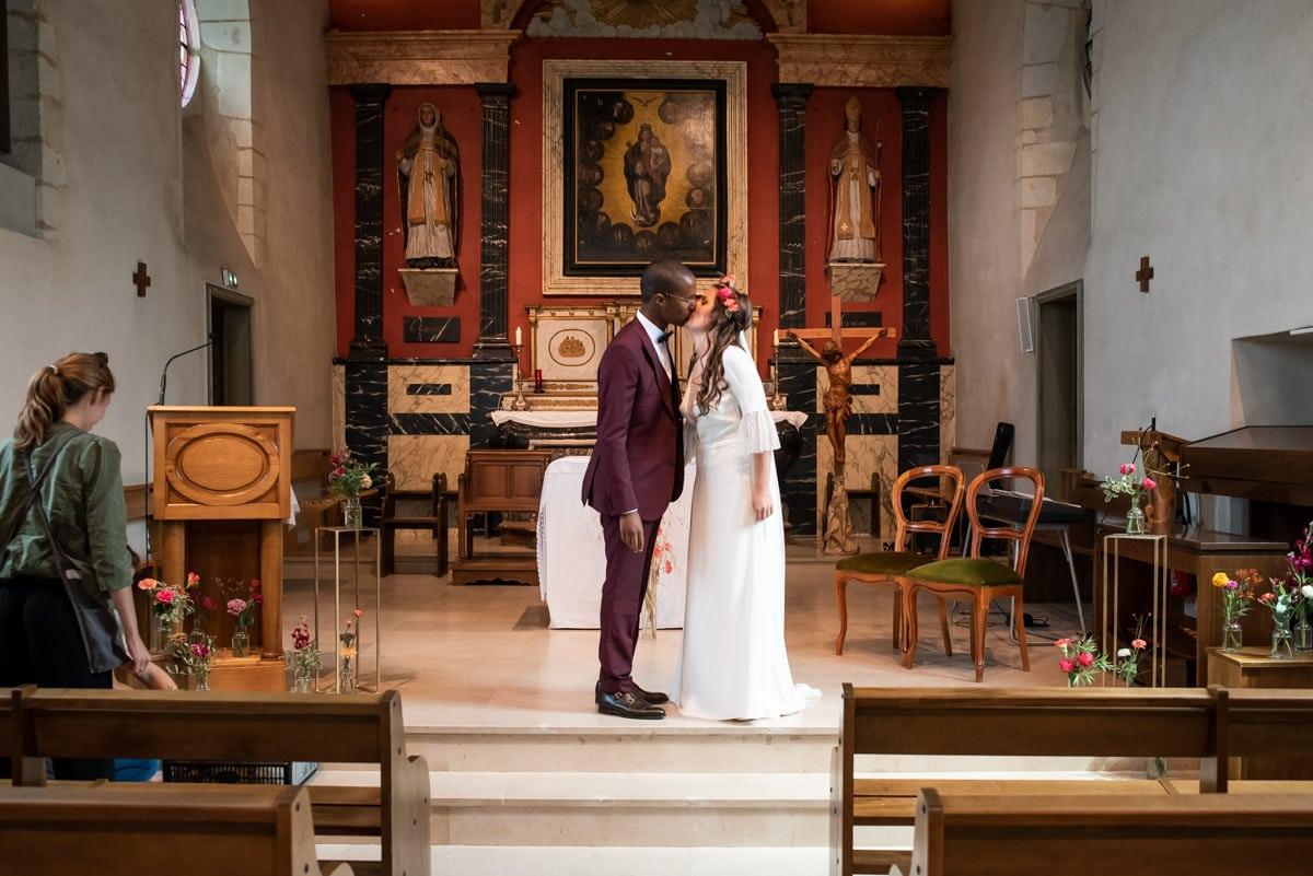 Les mariés s'embrassent devant l'autel et les fleurs de l'Atelier Aimer.