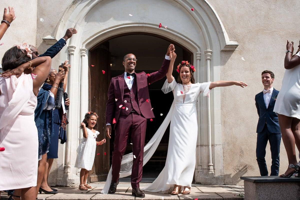 Les mariés sortent de l'église sous les pétales de roses.