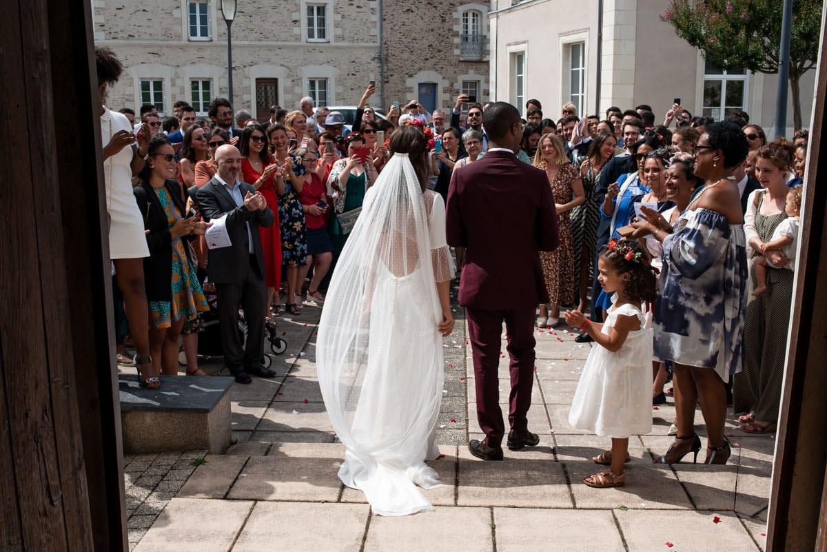 Les mariés de dos sortent de la cérémonie religieuse.