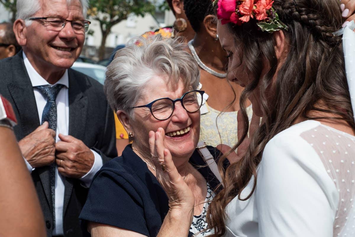 La grand mère de la mariée rigole en embrassant sa petite fille.