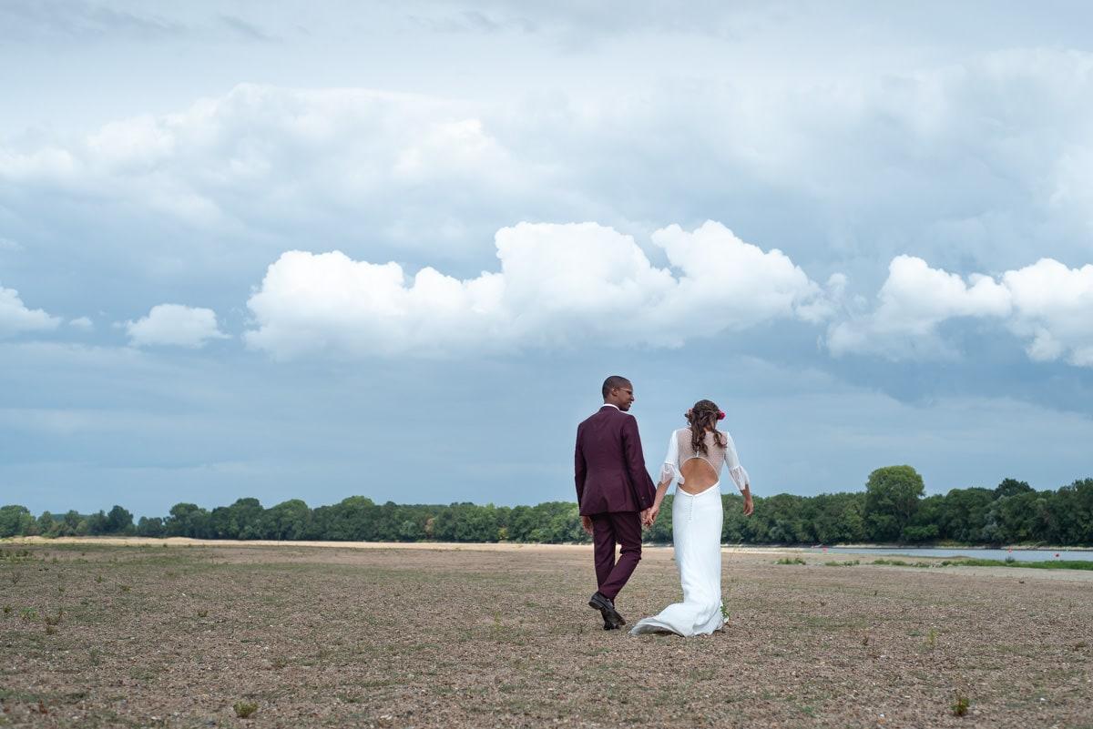 La robe Sophie Sarfati de la mariée vole au vent sur la plage de Béhuard.