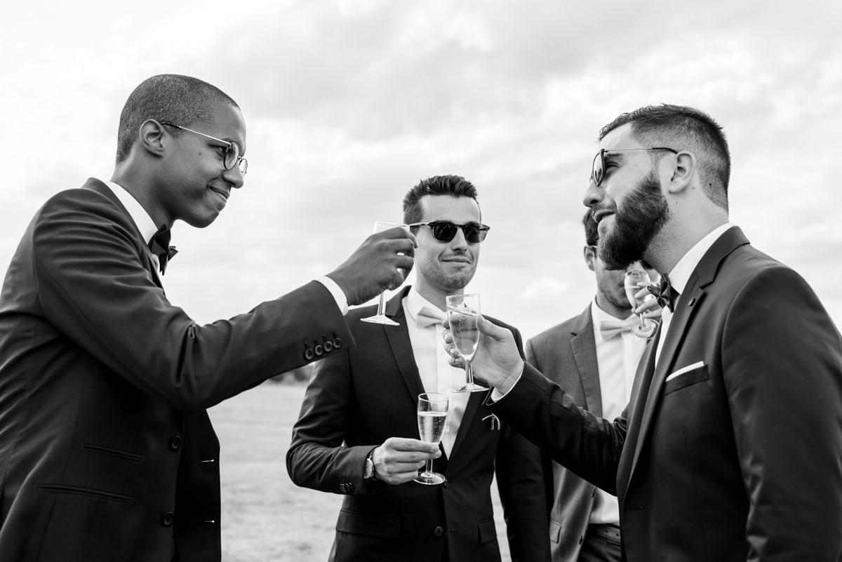 Photo de mariage en noir et blanc où le marié trinque au champagne avec ses amis à Rochefort sur Loire.