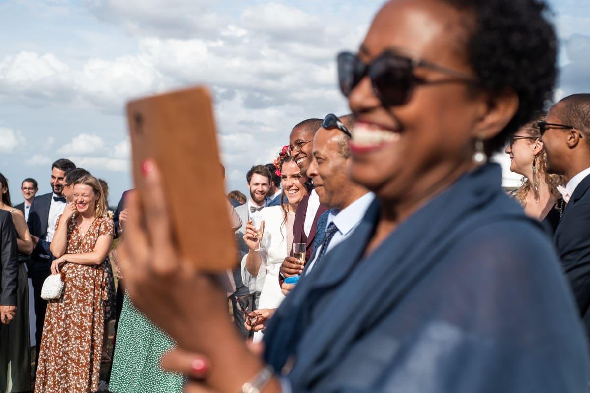Mariés et invités écoutent le discours en rigolant, une invité filme avec son téléphone.
