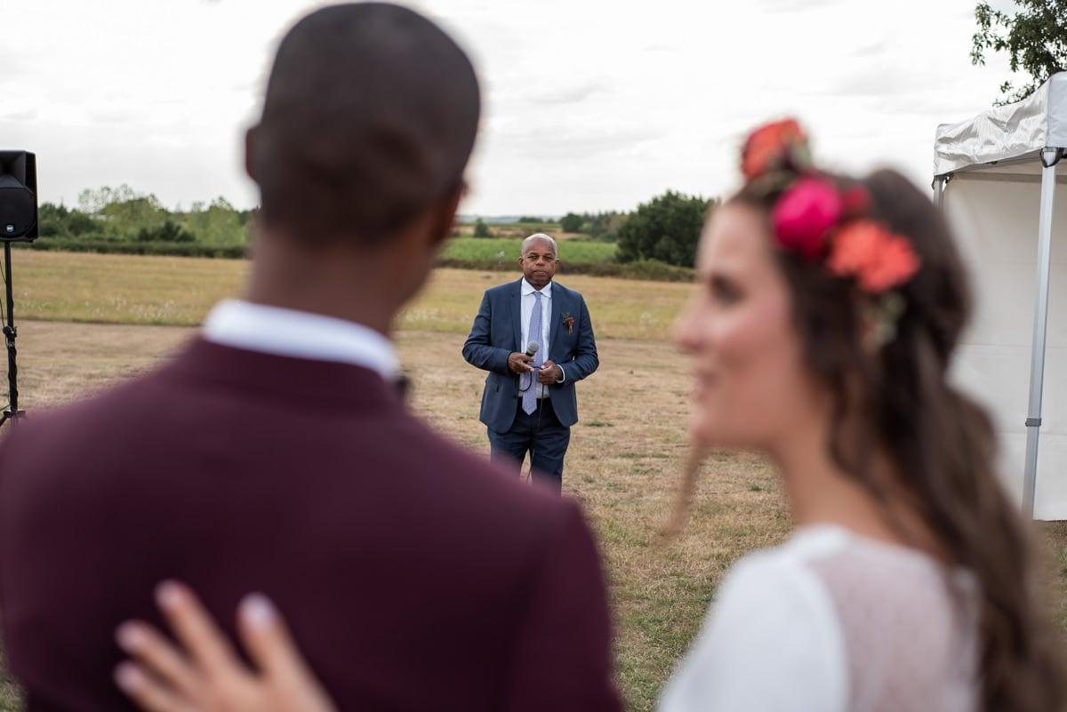 La mariée regarde son époux pendant le discours du père du marié.