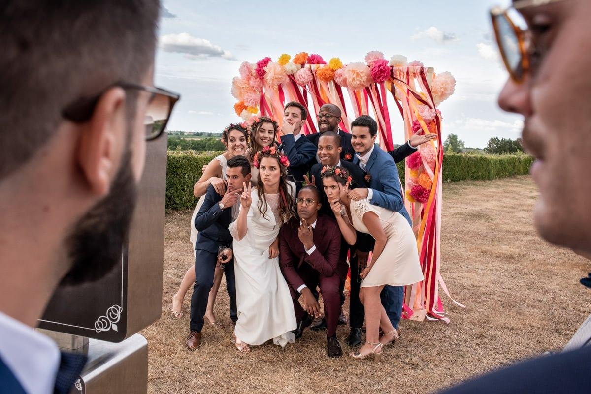 Un groupe d'amis grimançant devant une borne photo au mariage organisé à Rochefort sur Loire.