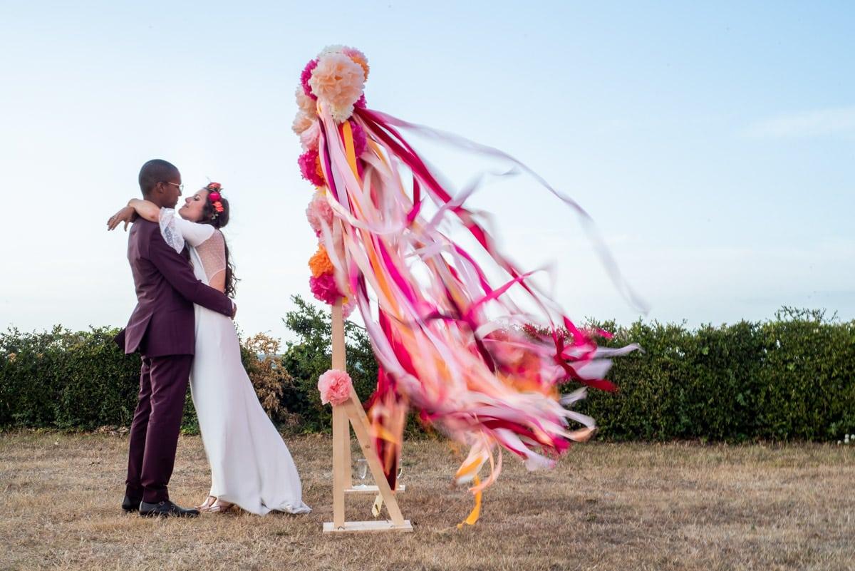 Les jeunes mariés dansent avec des boujies magiques derrière leur gâteau fleuri au château de l'Eperonnière