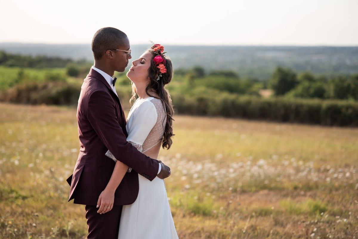 Photo de couple en face de Savennières, la mariée porte une couronne de fleurs roses et oranges de l'Atelier Aimer.
