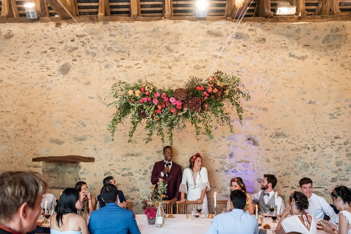Les mariés tout sourire sous un ciel de fleurs de l'Atelier Aimer, font un discours pour l'ouverture de le repas de mariage au château de l'éperonnière à Rochefort sur Loire.