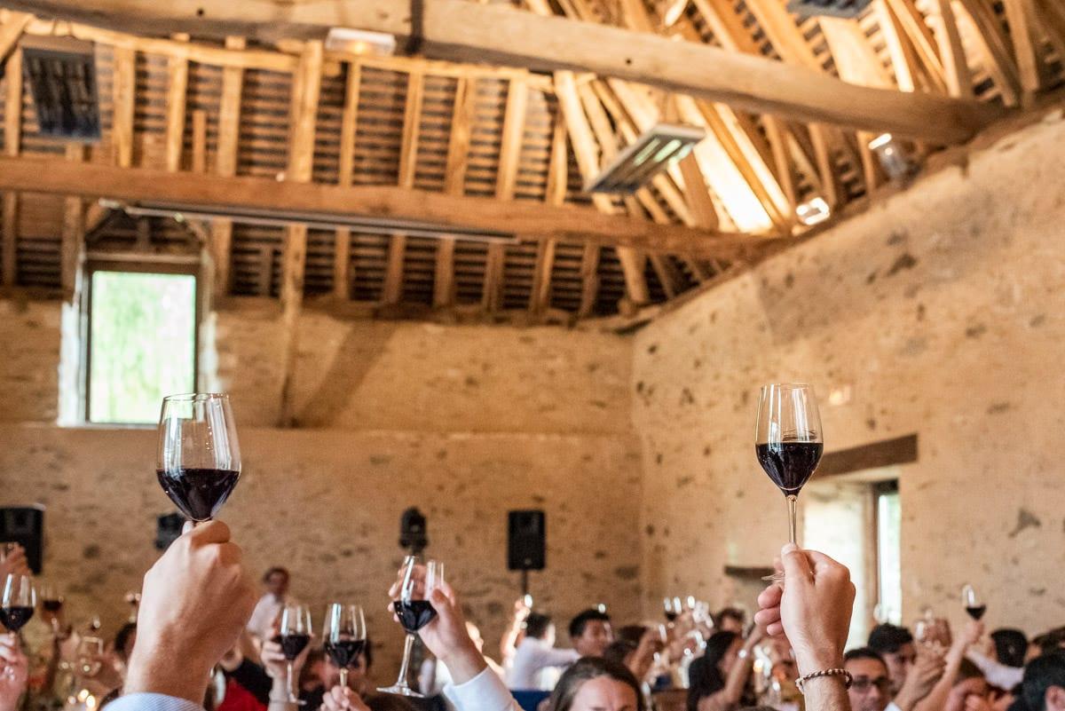 Les invités portent un toast en levant leur verre de vin rouge.