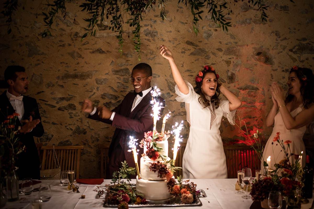 Les mariés dansent derrière leur gâteau de mariage fleuris.