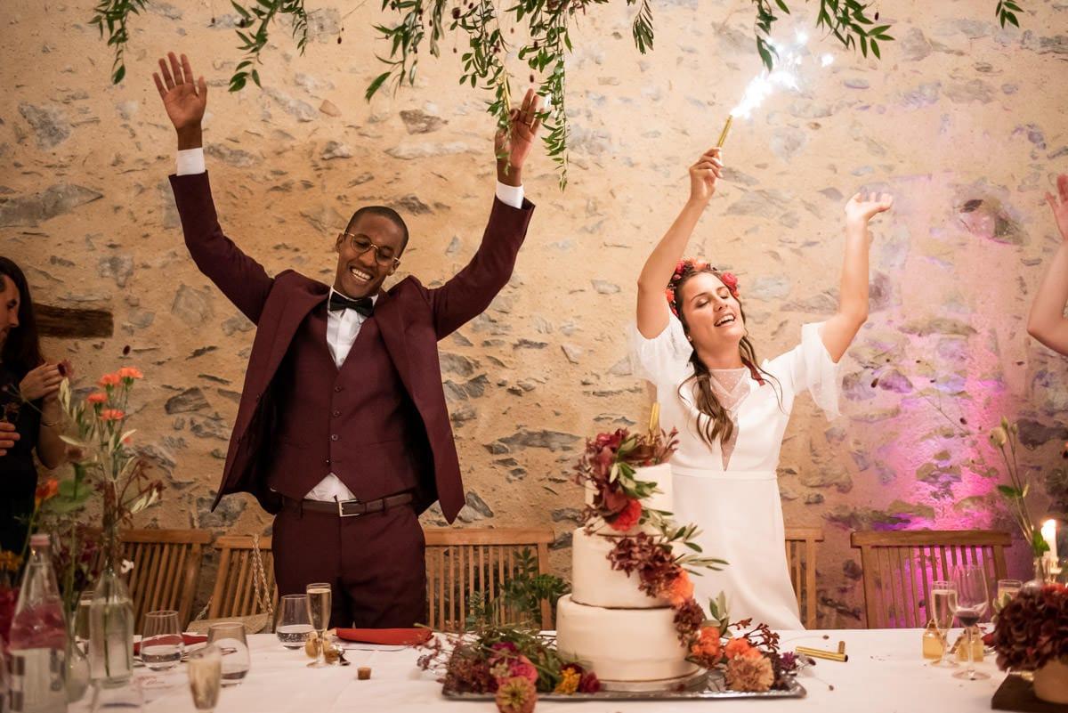 Les mariés dansent avec des bougies magiques derrière leur gâteau fleuris au chateau de l'eperonnière.