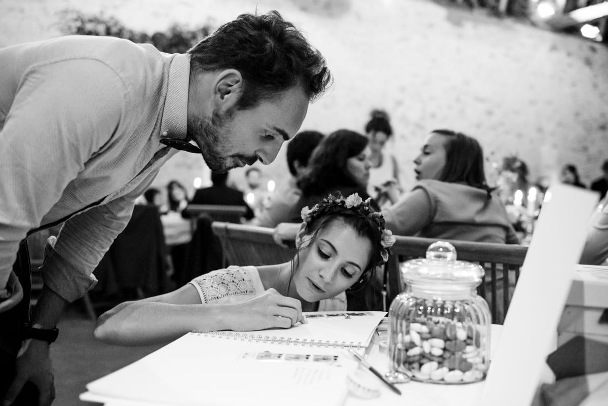 Photo de mariage en noir et blanc des invités qui écrivent dans le livre d'or.