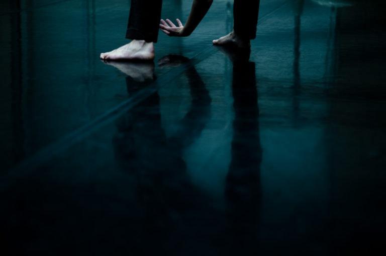 les pieds d'une danseuse se reflètent sur le tapis de danse noir du plateau du CCN de Pantin.