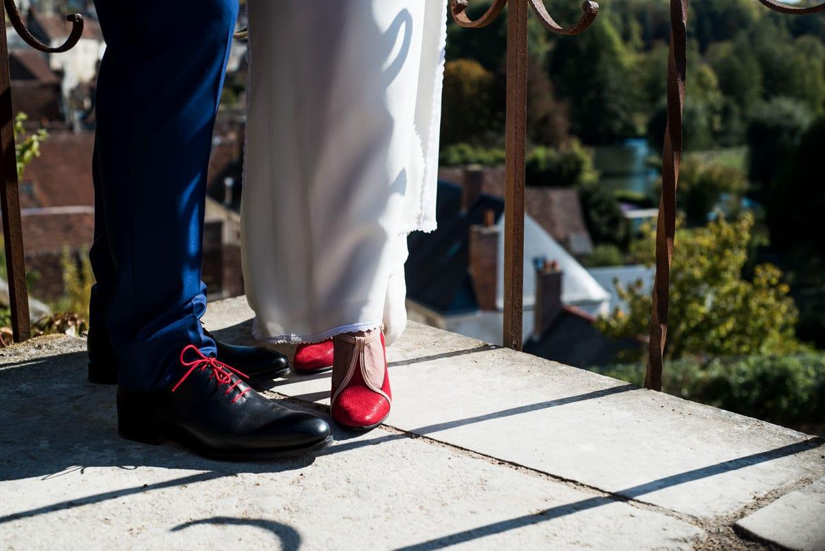 Les chaussures rouges de la mariée se coordonnent aux lacets rouges des chaussures du mariés, sur les toits de Montrésor.