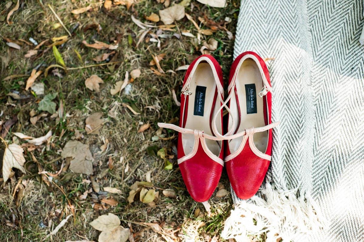 Les souliers rouges de la mariés sont posés sur l'herbe.