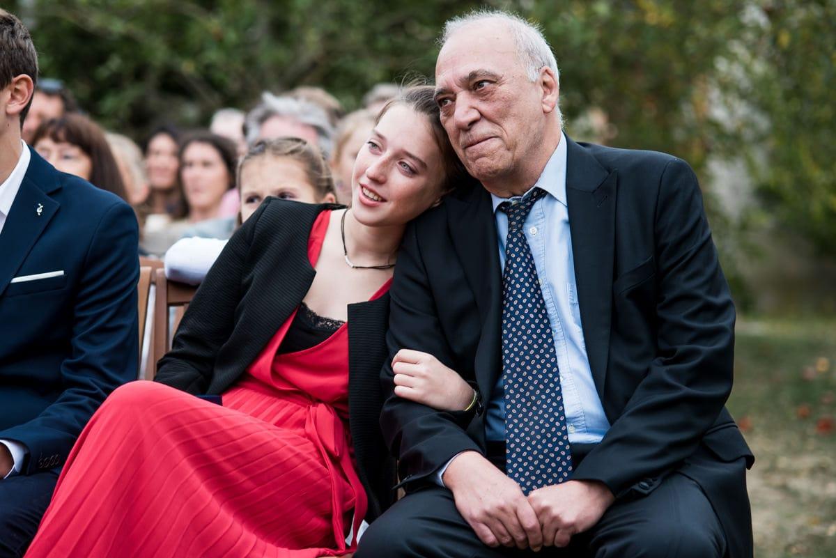 La petite fille et son grand-père écoutent le discours des témoins.