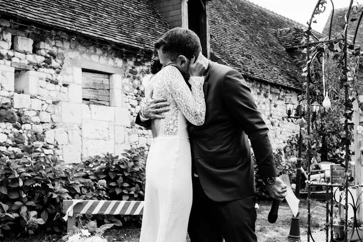 Les mariés s'embrassent sur cette photo en noir et blanc au domaine des 4 saisons.