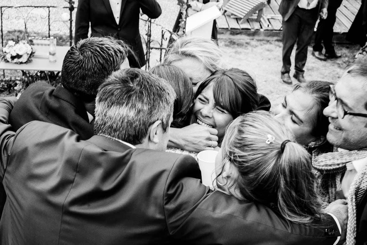 Grande embrasse de mariage sur cette photo de reportage en noir et blanc.