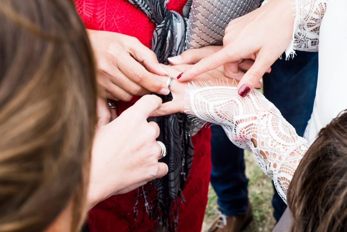 La mariée montre son alliance a ses amis.