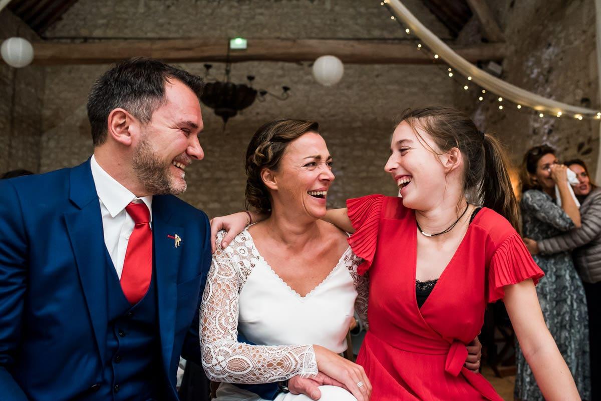 éclat de rire entre une fille et ses parents lors du mariage.
